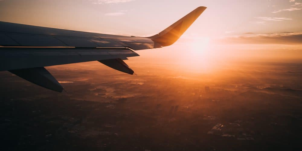 How to survive long flights in economy: Plane wing with sunset in background