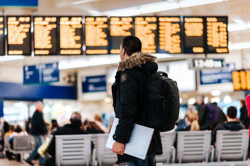 How to survive long flights in economy: Man standing in waiting hall of airport looking at screens blurred in the background, wearing a winter jacket and holding a laptop