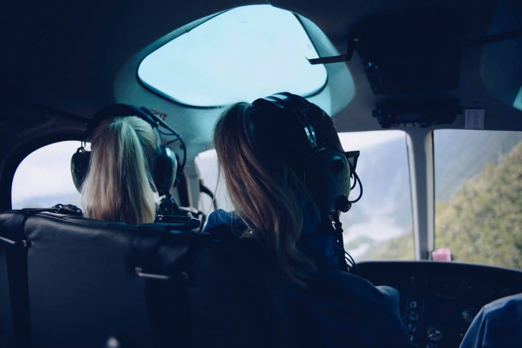 How to survive long flights in economy: Two girls sitting in a cockpit only seen from behind, they're wearing headphones