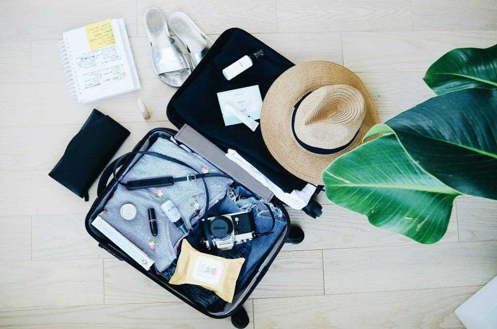 How to survive long flights in economy: Flatlay of open suitcase with travel accessories like sandals and beach hat lying on the floor