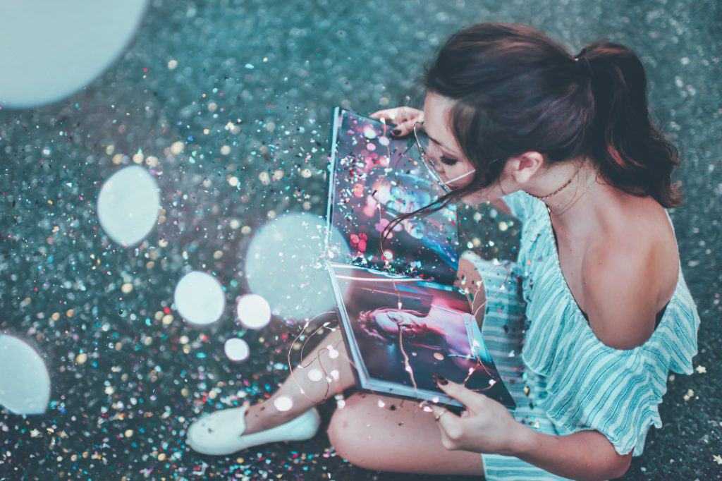 Healthy relationships, young woman with tied brown hair sitting on street reading a book, there is glitter all over the place