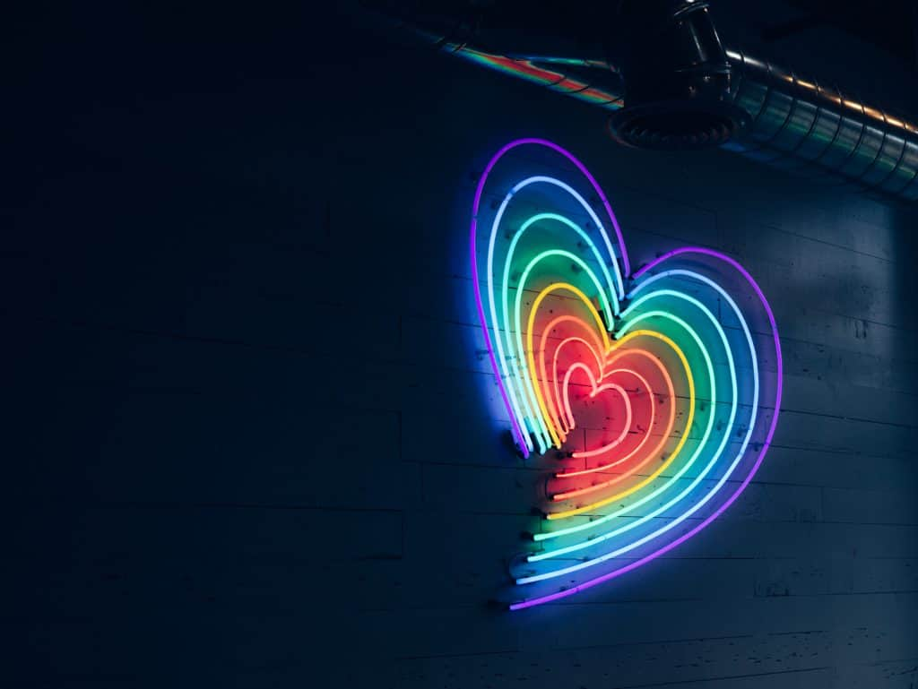 Healthy relationships, heart made out of neon lights in rainbow colors on black background