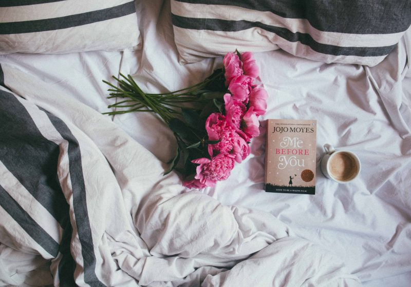 How to sleep better: Pink flowers lying in bed next to a book and a mug of coffee