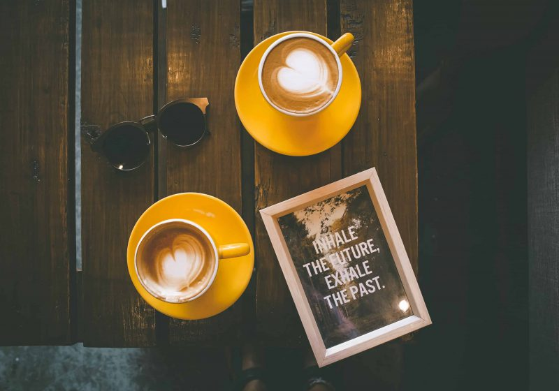 How to stop gossiping: Two coffees in yellow cups with white milk hearts, sunglasses and little picture with quote 'inhale the future, exhale the past' lying on wooden table