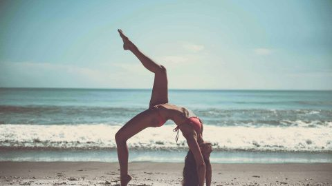 Yoga: Brunette girl doing a bridge pose holding one leg up to the sky and wearing a red bikini. She's on the beach and the sea is in the background.