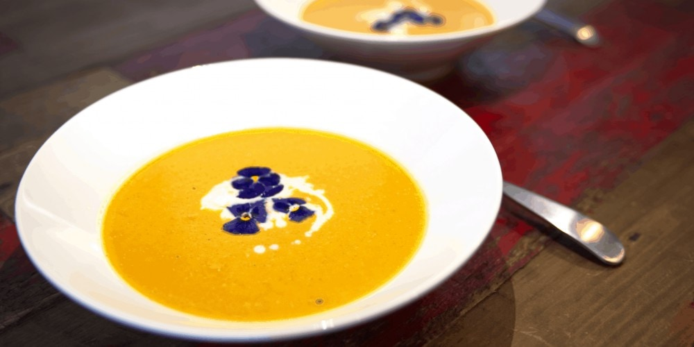 Pumpkin Soup in two white bowls on wooden table