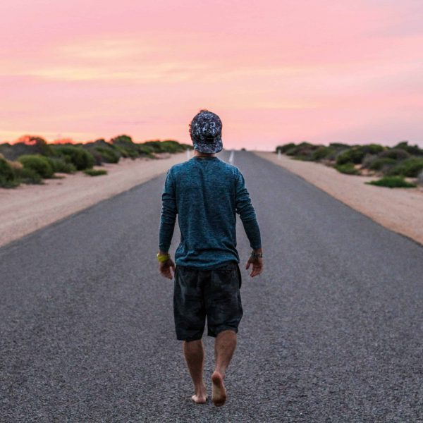Man walking on empty road in front of pink sky, Choosing yourself