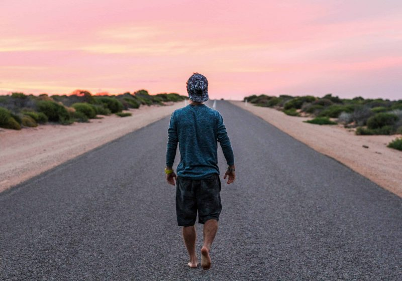 Man walking on empty road in front of pink sky, Choosing yourself