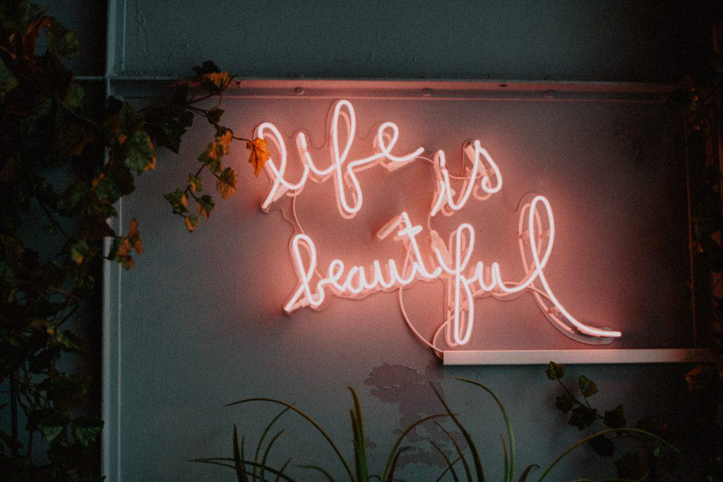 Neon sign in light pink saying life is beautiful - How to let go. Life lessons I wish I knew earlier in life.