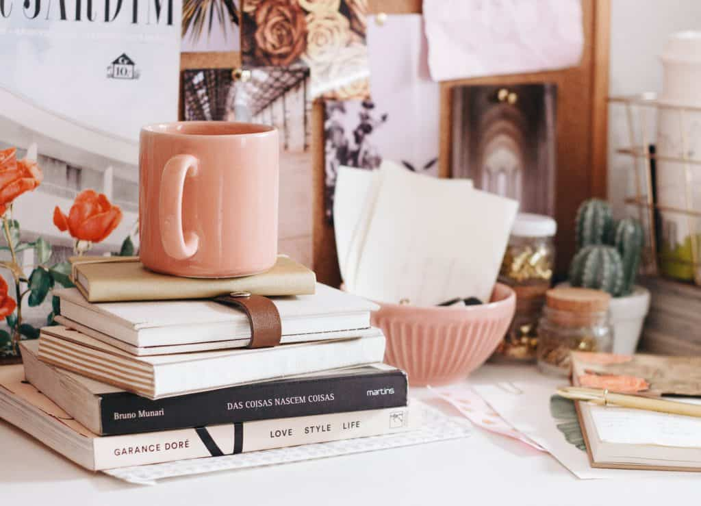 A collection of books on a table with a light pink coffee mug - How to let go. Life lessons I wish I knew earlier in life.