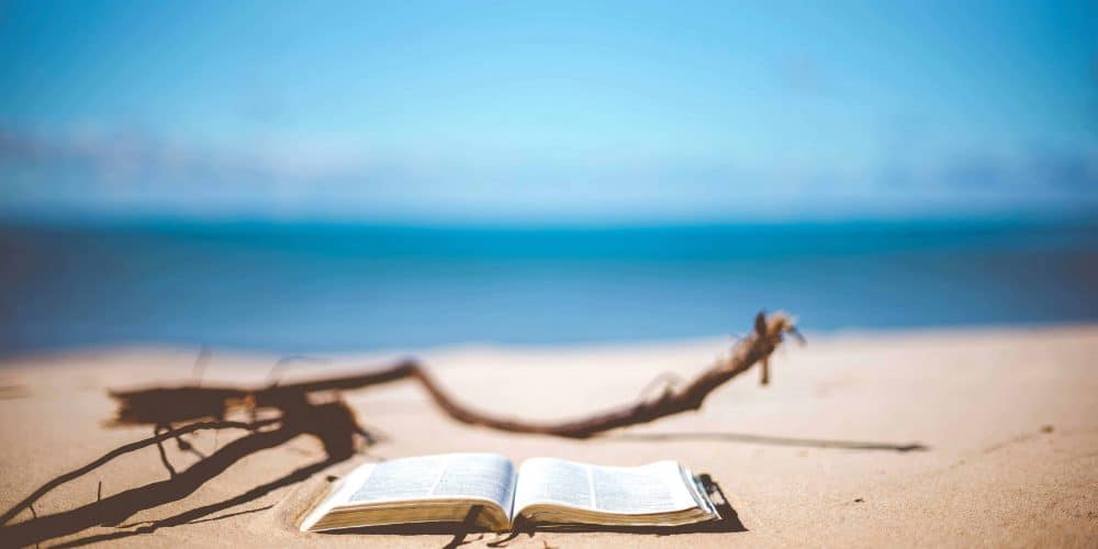 Book laying on the beach, Travel Reading List 2019 by A gorgeous Soul