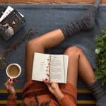 Girl sitting on floor with thick socks and sweater book in her lap and cup of hot beverage in hand