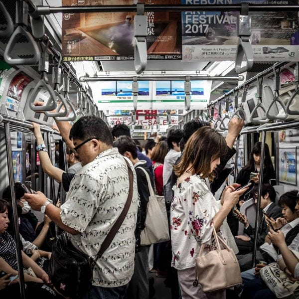 People standing in subway and staring into smartphones