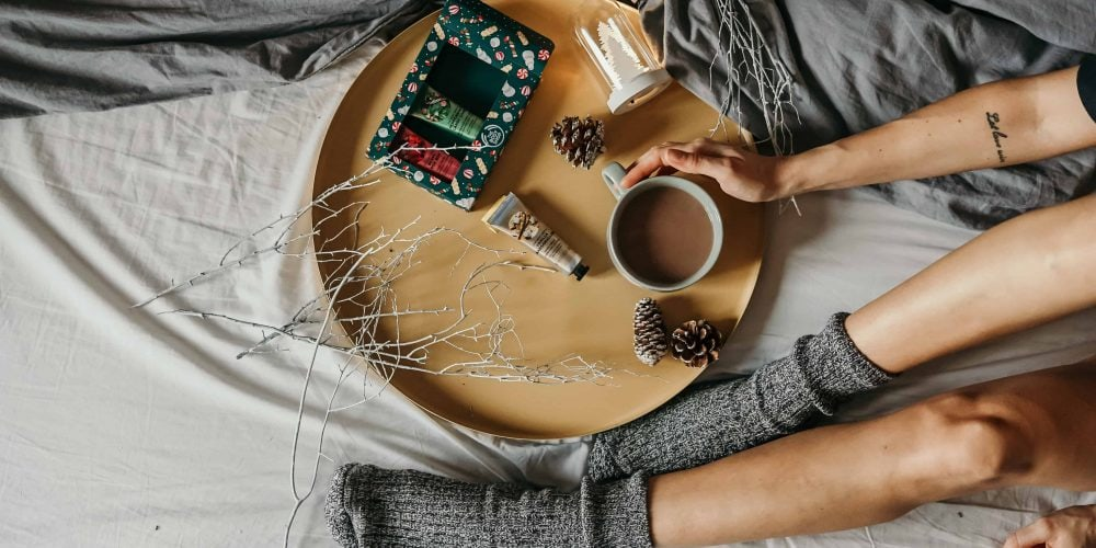 Flat Lay of a cozy day in bed with hot drink, hand cream, warm socks