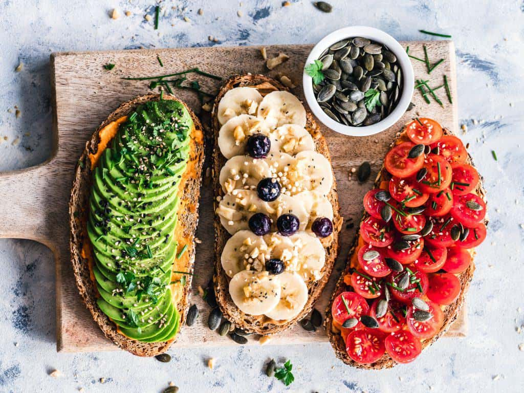 Flatlay of three open sandwiches with avocado, banana and tomato slices on a chopboard