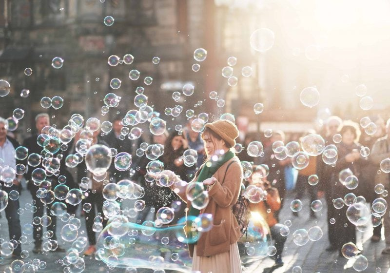 GIrl outside with lots of bubbles around her