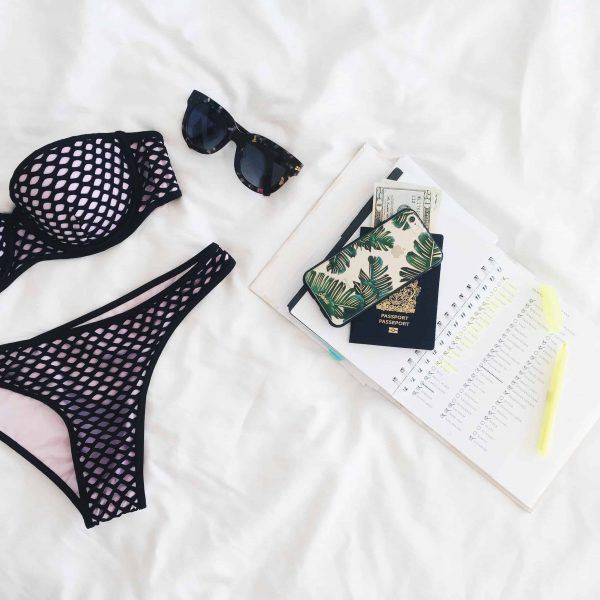 flatly of black bikini, black sunglasses and passport on white bedsheet - 44 best travel accessories and 20 secret travel hacks to survive long flights in economy