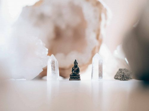Little buddha figure in front of crystals and minerals