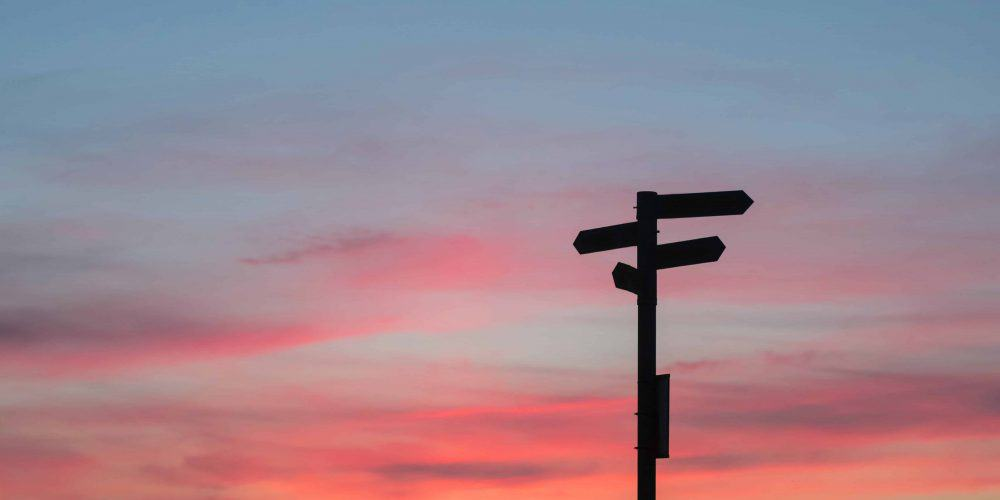 the silhouette of a couple of signs pointing in different directions in front of a sunset