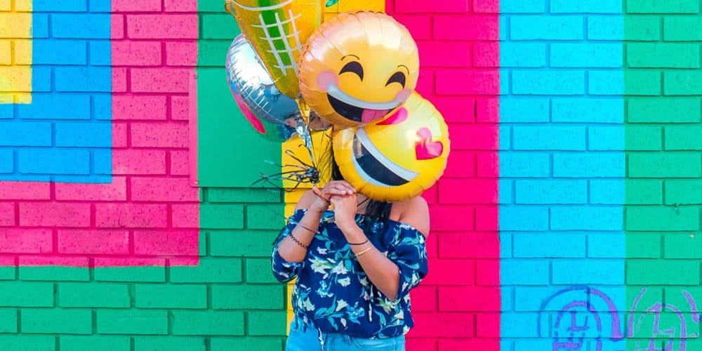 Woman standing in front of colored wall with fun balloons