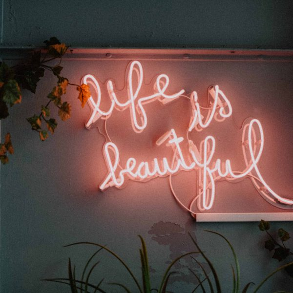 Neon sign in light pink saying life is beautiful - Mindful & Healthy Habits